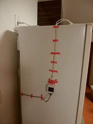 冷蔵庫の側面の低い位置にマスキングテープで固定された測定器の写真。約10センチ置きにテープが貼られている。